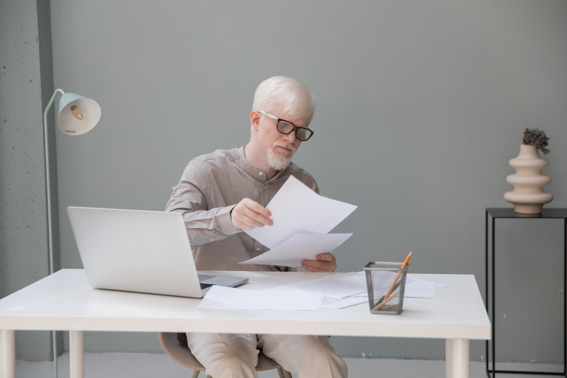 man with white hair reading a paper